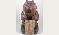 Вырезана скульптура из дерева. Медведь с бочкой.